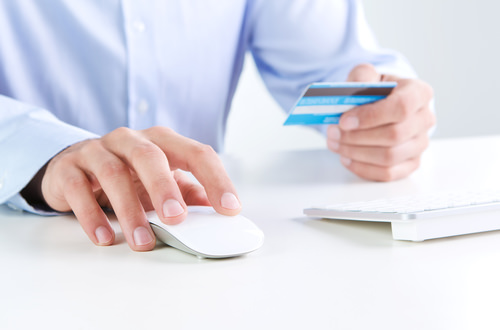 PersonUsingPaymentCardOnlineShopping Huge business data breach in Scam Awareness Month