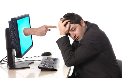 Stressed man in front of computer Keeping Businesses And Individuals Safe Online